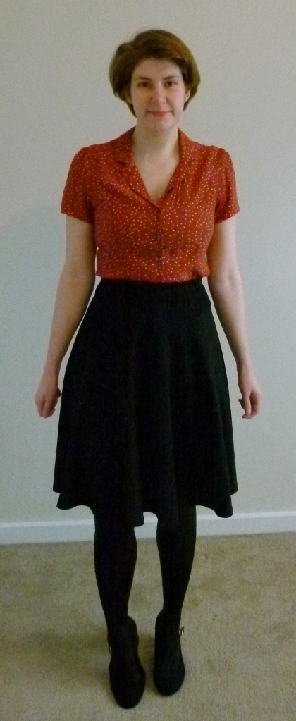 Full length photo of Helen wearing an orange tea-dress style top with white polka dots, a black circle skirt, black tights, and black Mary Jane courts with a gold buckle.