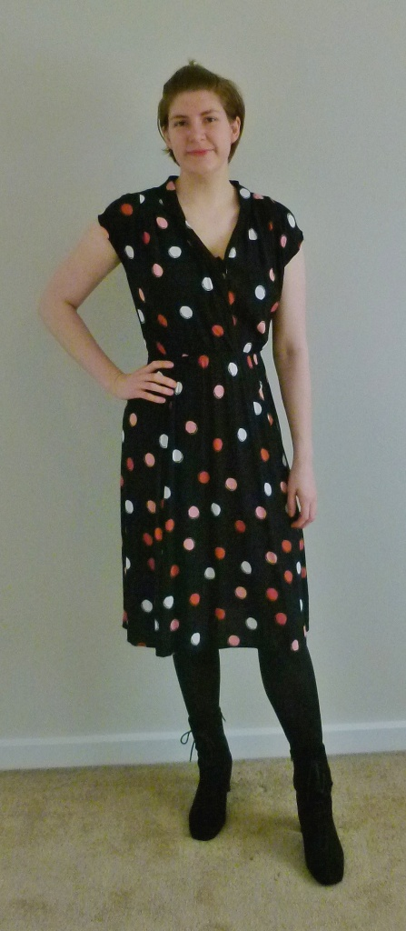 Full length photo of Helen wearing a black cap-sleeved dress with large pink, white and peach coloured polka dots, black  tights, and black suede lace-up boots.