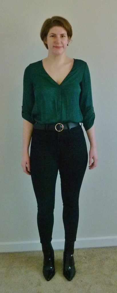 Full length photo of Helen wearing a green silky, three-quarter length sleeved V-neck top, black high-waisted skinny jeans, and black croc-effect boots.