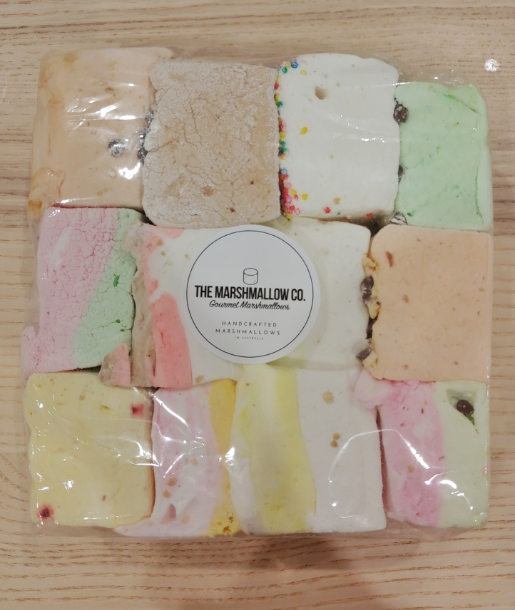 Close up of a flat bag of large, colourful chunks of marshmallows cut into large squares.