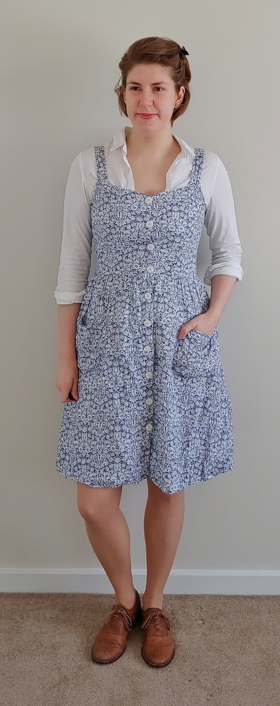 Full length photo of Helen wearing a knee-length pinafore dress with white buttons down the centre front, and patch pockets with a gathered skirt, in a white floral on blue pattern.  Underneath is a simple collared white shirt with the sleeves rolled up to te elbows.