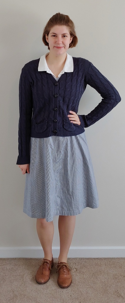 Outfit as above, with the addition of a navy blue cable-knit cardigan with faux-horn buttons down the front.