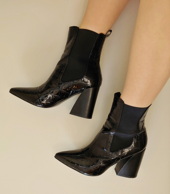 Close up of Helen wearing shiny black crocodile-skin look pull on boots with a chunky heel and pointed toe.