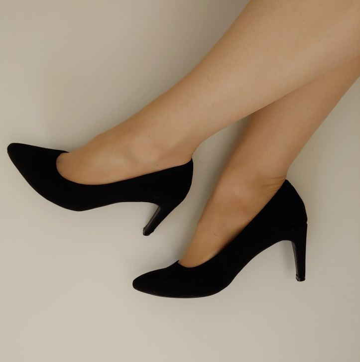 Close up of Helen wearing black pointy high-heels with a thin heel.