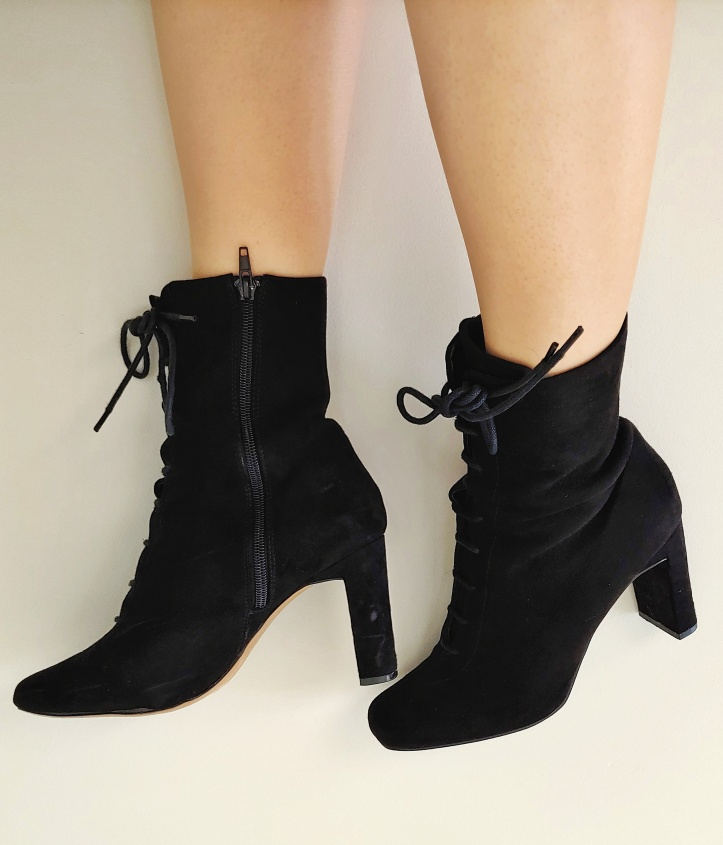 Close up of Helen wearing black lace-up suede boots with a high heel.