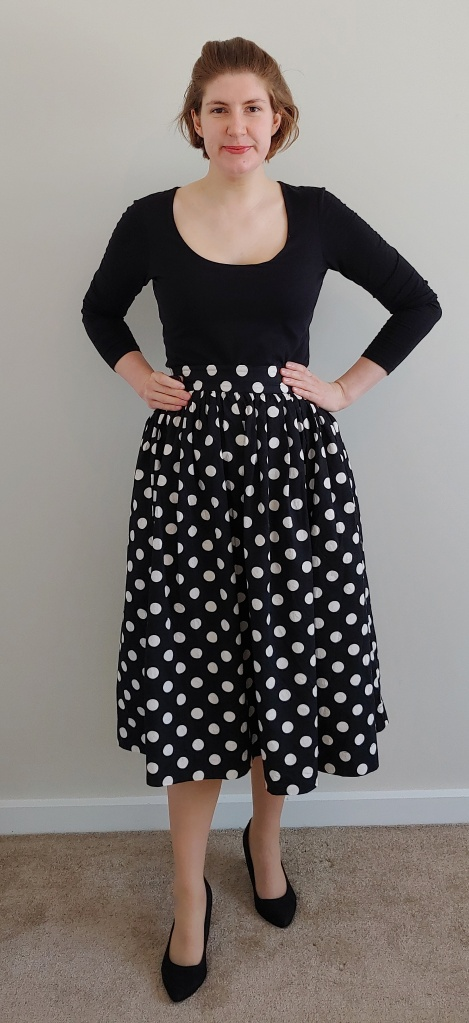 Full length photo of Helen wearing a scoop-neck long-sleeved T-shirt with a long, over-the-knee circle skirt with white spots on a black background.