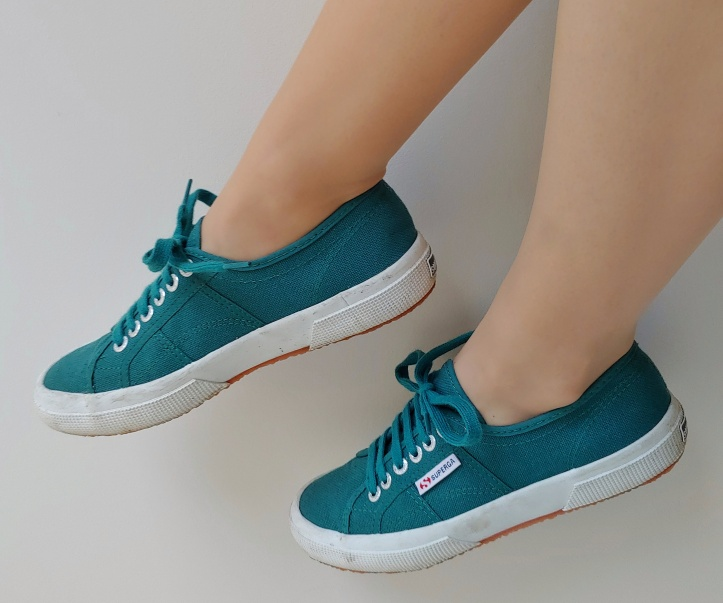 Close up of Helen wearing greeny low-top Supergas with white bases and green laces.