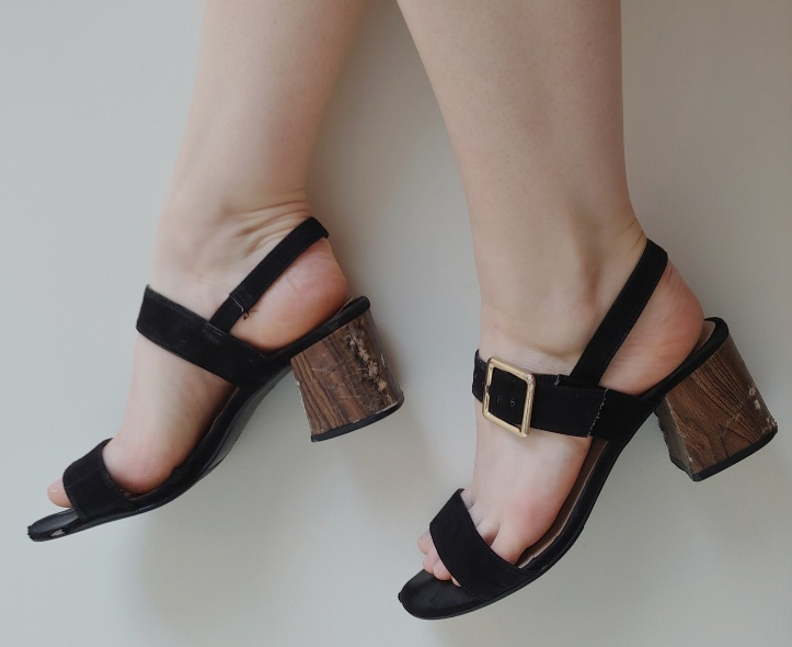 Close up of Helen wearing black block heeled sandals with a wood effect heel, against a white background.