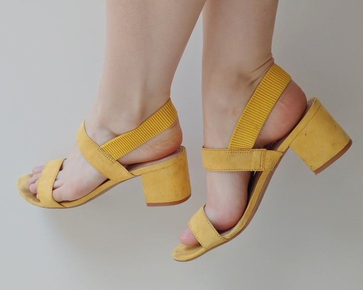 Close-up of Helen wearing yellow block-heeled strappy sandals