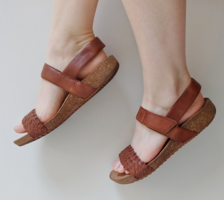 Close up of Helen wearing light brown sandals with a cork effect base and a plaited leather front strap.