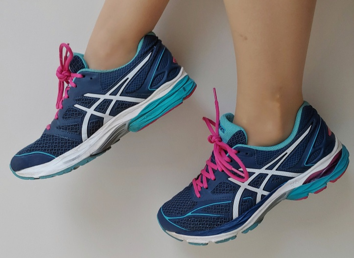 Close up of Helen wearing blue, turquoise and white running shoes with bright pink laces.
