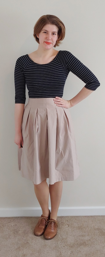 Full length photo of Helen wearing a beige knee-length pleated skirt with a black and thin white horizontal striped top with half-length sleeves