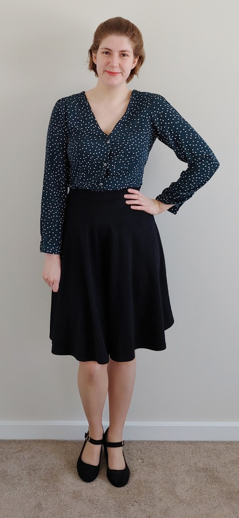 Full length photo of Helen wearing a dark turquoise blue long-sleeved top with small white polka dots, A black circle skirt, and black Mary-Jane shoes.