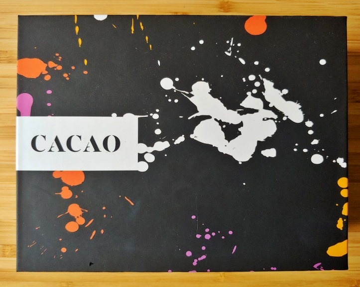 Black box with white, yellow, orange and purple paint splotches, and 'CACAO' on a white text box.