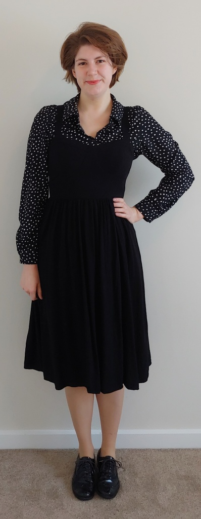 Helen wearing the black pinafore dress with a long-sleeved collared shirt underneath, with small, creamy-white polka dots on a black background.