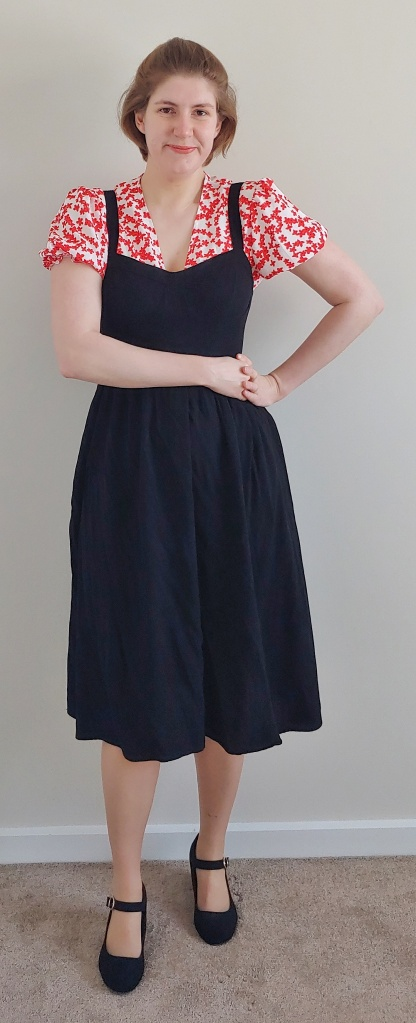 Full length photo of Helen wearing a black knee-length pinafore dress with a short puff-sleeved top with red flowers on a white background, and black Mary-Jane shoes.