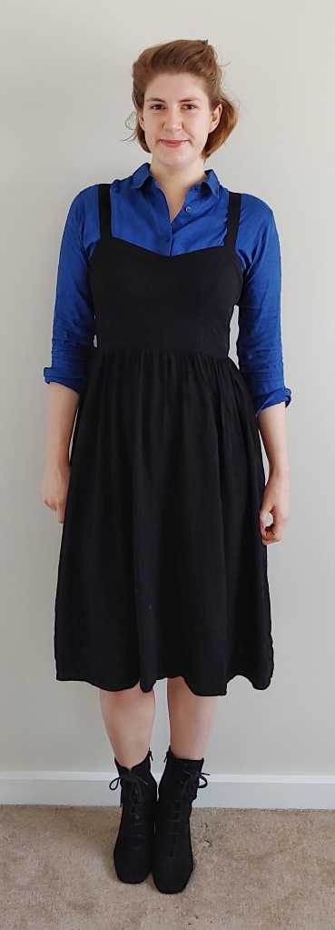 Helen wearing the pinafore dress with a rich, dark blue linen shirt underneath with the sleeves rolled up to three-quarter length, and black faux-suede boots.