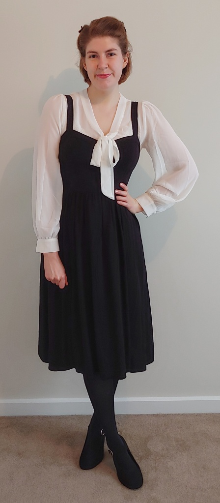 Helen wearing the pinafore dress with a long-sleeved, sheer white pussy-bow blouse underneath, black tights, and black Mary-Jane heels.