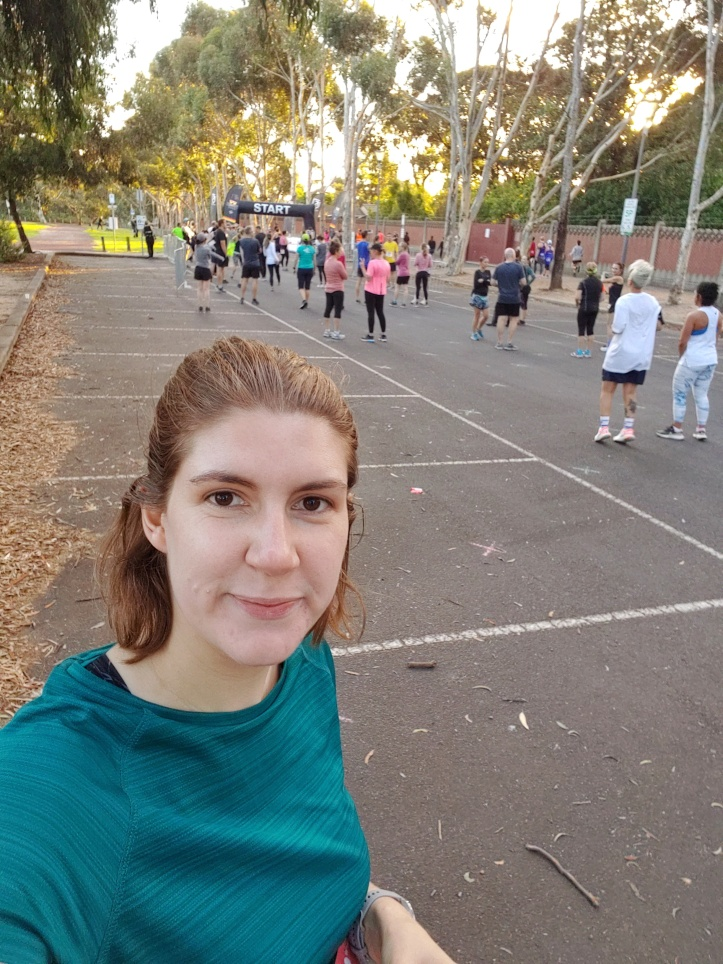 Selfie photo of Helen at the start line, with other runners and tall gum trees in the background.