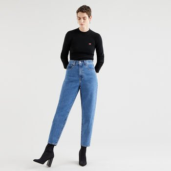 Catalogue image of a woman wearing blue mid-wash high-waisted tapered jeans, with black high-heeled boots and a black long-sleeve top.