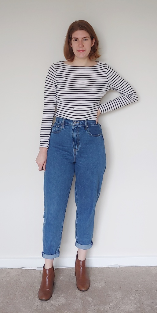 Helen wearing the jeans with cuffed ankles, brown boots, and a white and navy long-sleeved Breton.