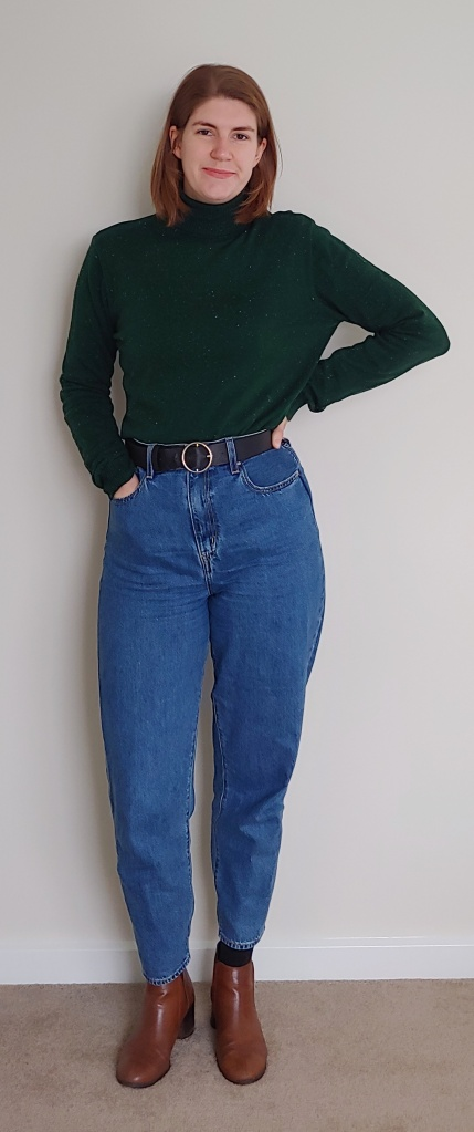 Helen wearing the blue mid-wash Levi Loose Taper Jeans, with a black belt, brown low-heeled boots, and a dark green turtleneck.