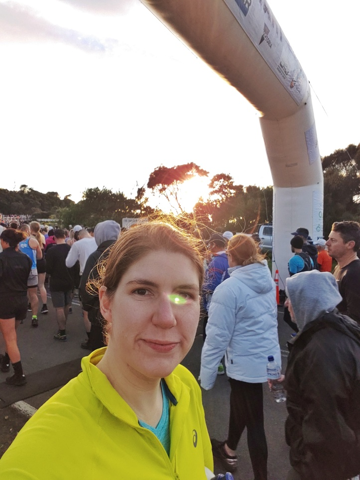 Helen facing the camera under the start line of the race.