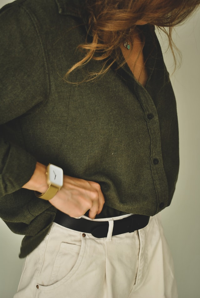 A woman with long brown hair wearing a large green shirt and cream chinos with a black belt. Close-up on the belt