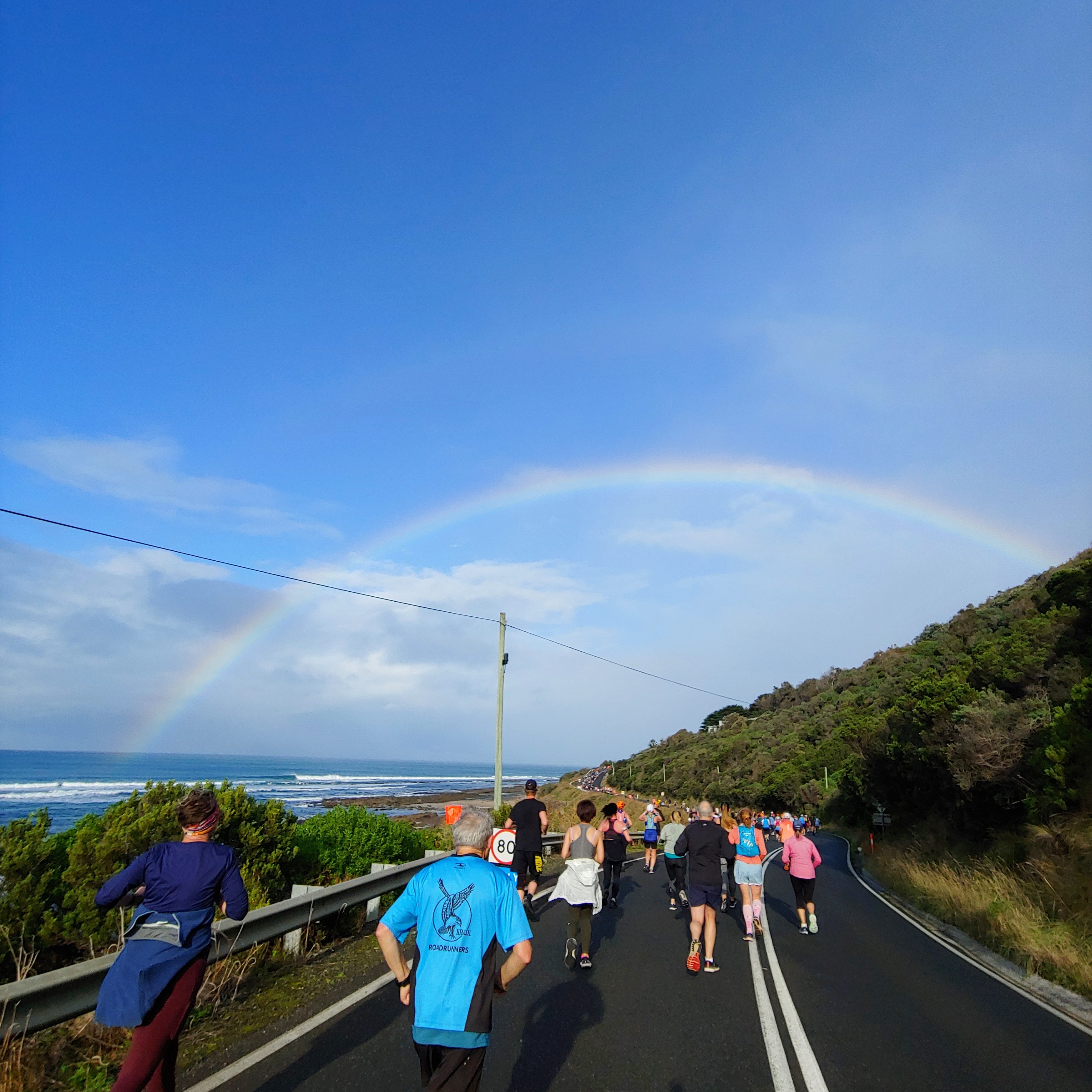 People running along a tarmac road with woods on the right and the sea on the left, and a bright rainbow in the sky overhead.