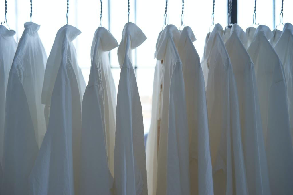 Line of white shirts hung on a clothing rail.