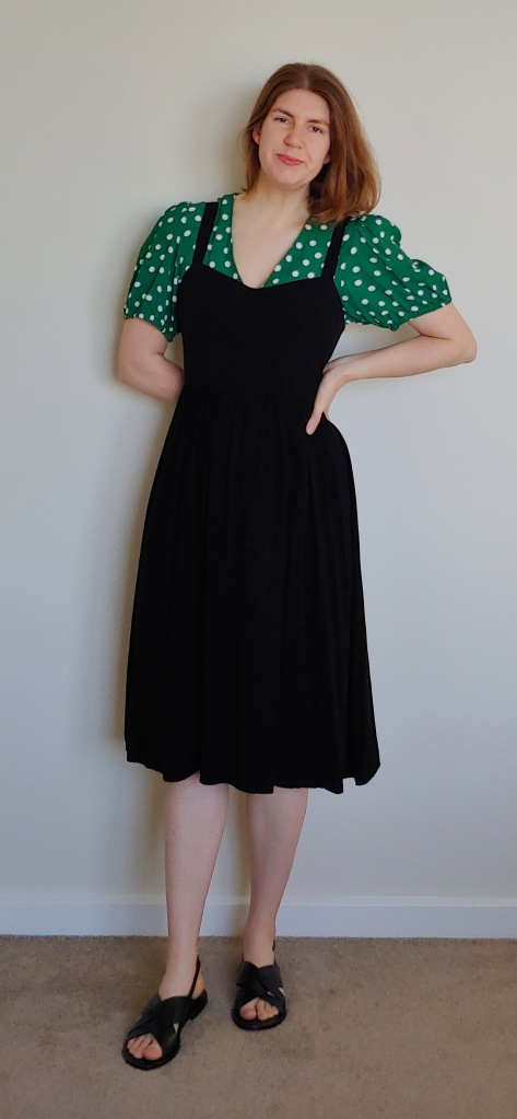 Helen wears a grass-green puff-sleeved shirt with medium-sized white polka dots, and a black pinafore dress, with black sandals.