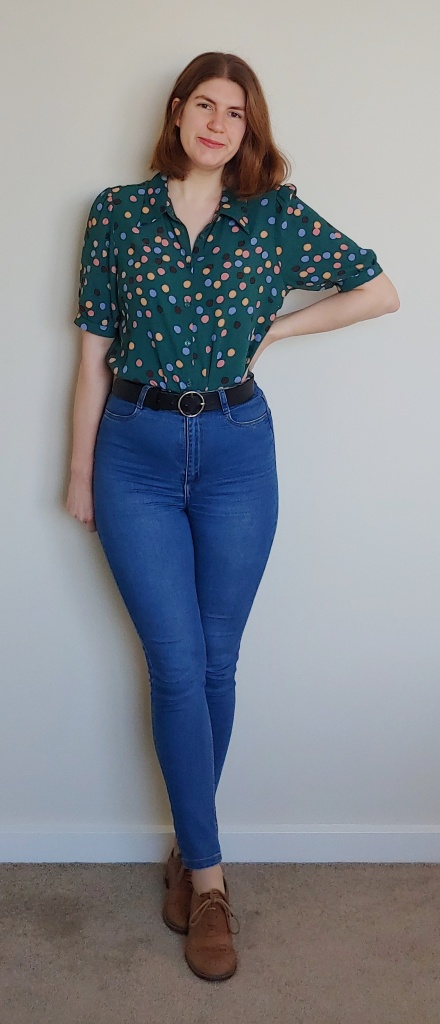 Helen wears blue skinny jeans and a teal-green blouse with medium-sized polka dots in dark blue, light blue, pink and beige. She also wears brown brogues.