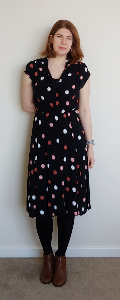 Helen wearing a black mid-length dress with medium-sized pink, coral pink and white polka dots. She also wears black tights and brown ankle boots.