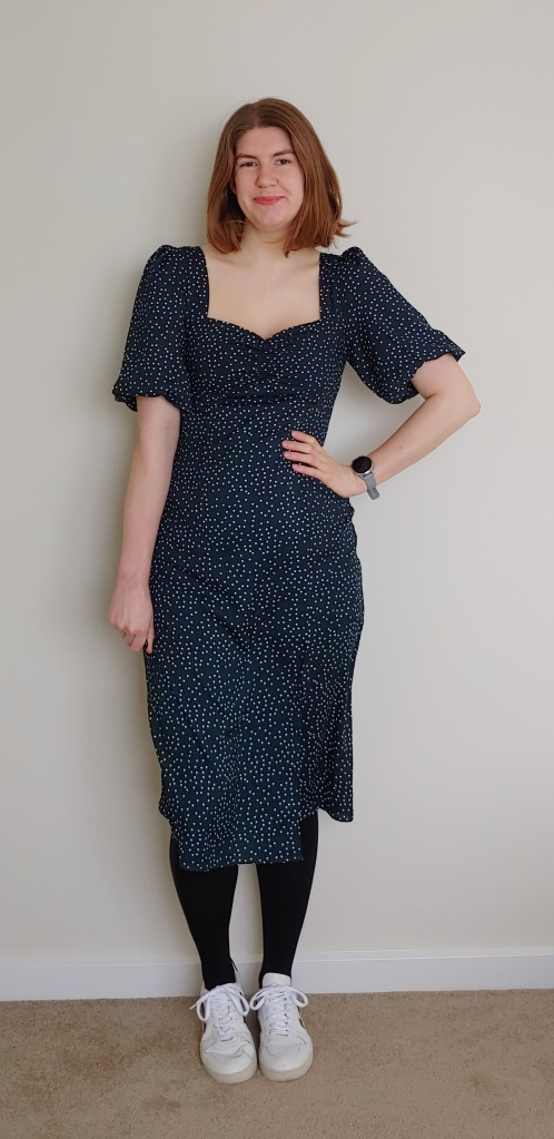 Image of Helen wearing a dark green mid-length dress with small white polka dots, with black rights and white sneakers.