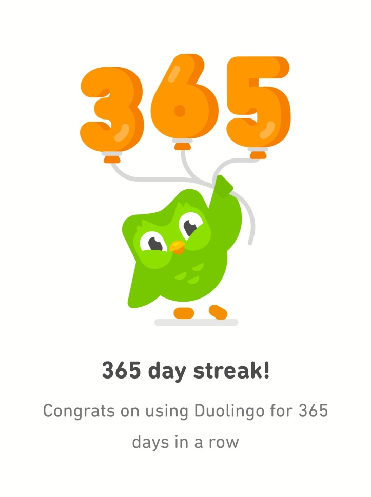 Cartoon image of a green owl holding orange balloons spelling '365', with the message '365 day streak! Congrats on using Duolingo for 365 days in a row' beneath.